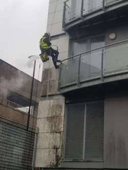 Abseiling technician industrial pressure washing tower block