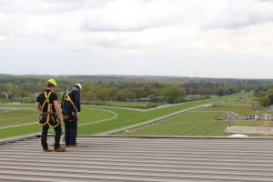 Two workers overlooking roof edge