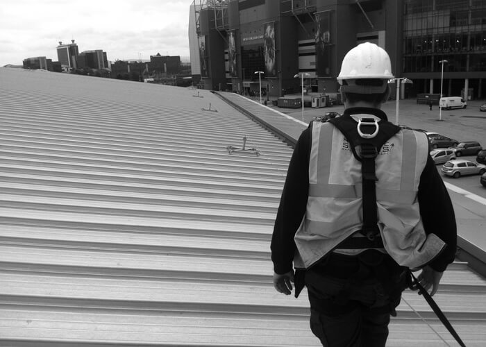 Man using Safety Line System on a metal deck roof