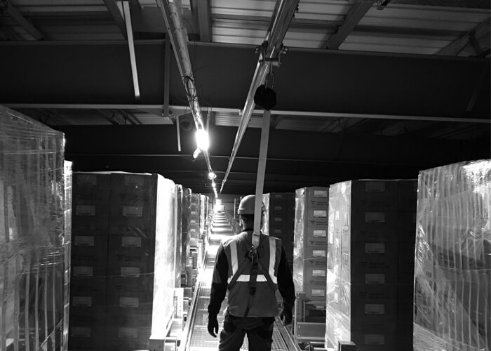 Man using an Overhead Fall Arrest Track in warehouse
