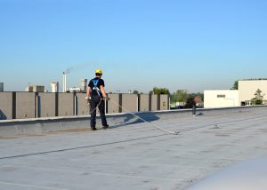 Man Working at Height on a Flat Roof Attached to a Safety Line